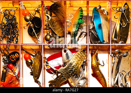 A plastic box full of artificial lures for fishing with a spinning rod. - Stock Image