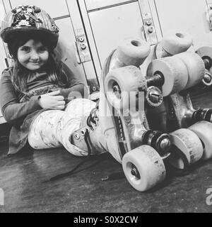 Toddler girl sitting wearing roller skates. - Stock Image