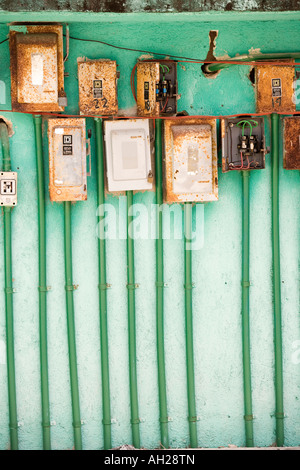 Many rusted electric panels on a green wall - Stock Image