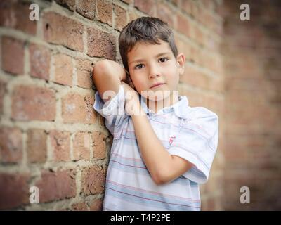 Boy, 7 years, leaning against a wall, Portrait, Germany - Stock Image