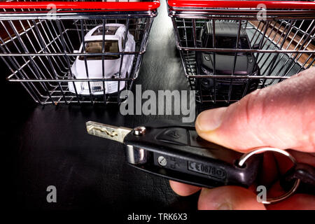 Buying a car concept: Fingers on a key fob in the foreground, with model cars in model shopping baskets in the background. - Stock Image