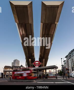 London, England, UK - May 28, 2019: Buses pass under the distinctive cantilevered roof of Vauxhall Bus Station in South London at dusk. - Stock Image