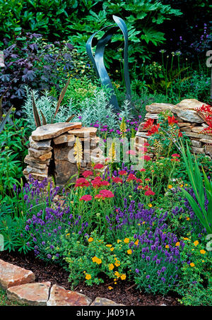 Colourful garden corner with dry stone wall and colourful plants - Stock Image