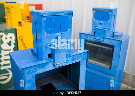 A pair of surplus newspaper boxes possessing human-like expressions sit behind a building in Springdale, Ark. - Stock Image