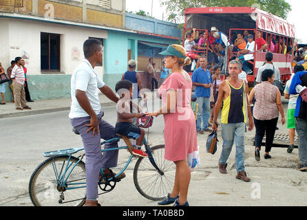 Granma, Cuba-April 04,2016: Streetlife scene at a corner in a ordinary street with people sitting in a truck, used as public transport - Stock Image