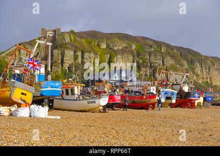 Hastings fishing trawlers pulled up high on the Old Town Stade beach on a stormy day in winter, East Sussex, UK - Stock Image