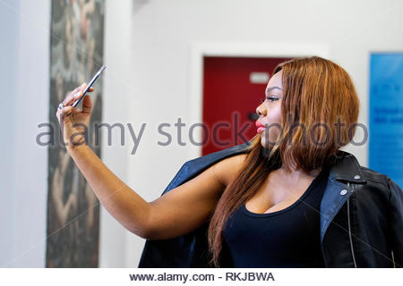 An African female student Nse Udohaya from Nigeria is taking videos of herself on her Apple Iphone inside the Dundee University, UK - Stock Image