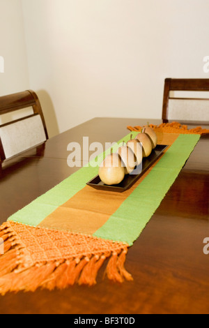 Artificial pears on a dining table - Stock Image