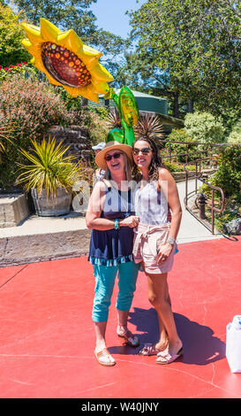 Two female Millennials celebrate one of their birthdays with a huge sun shaped mylar baloon on the patio at the Nepenthe restaurant on highway 1 in Bi - Stock Image