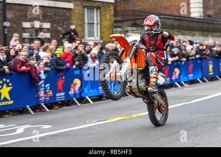 Moto Stunts International motorbike display team at London New Year's Day Parade. Motorcycle wheelie in Whitehall with Nelson's Column - Stock Image