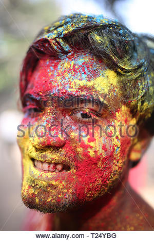 People celebrate Holi festival in Dhaka, Bangladesh on March 21, 2019. Holi is the festival of colors, fun and frolic and is celebrated by millions of Hindus in the Indian subcontinent to welcome the spring. An ancient Hindu festival, Holi is marked as a triumph of good over evil, and has become popular among non-Hindu populations in South Asia. In Bangladesh, many members from the Muslim community also join their Hindu neighbors to celebrate the festival by smearing abeer (a colored powder) and spraying water colors on each other. - Stock Image