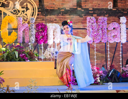 A woman in traditional costume dancing during the Chiang Mai Flower Festival in Thailand - Stock Image