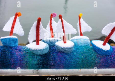 Yarn Bombing decorating public place with knitted objects here small sailing boats at Sunderland Marina - Stock Image