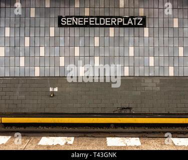 Berlin, Senefelderplatz Underground U-bahn railway station. Station name on grey tiled wall - Stock Image