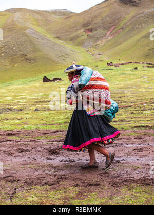 Vinicunca, Peru - January 7, 2017. View of a woman carrying food in the Vinicunca mountain. - Stock Image