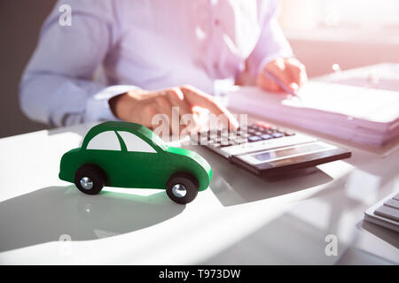 Close-up Of Car In Front Of Businessperson Calculating Bill - Stock Image