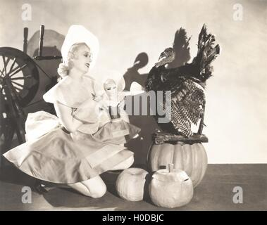 Woman holding doll wearing identical Thanksgiving costume - Stock Image