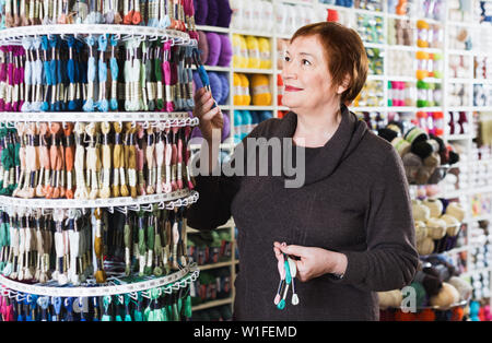 Glad cheerful  smiling woman choosing mouline for embroidery in needlework shop - Stock Image