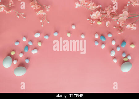 Pastel Easter eggs, malt candy covered chocolate eggs, and flower blossoms over a coral colored background with copy space. Image shot from top view. - Stock Image