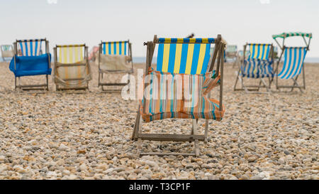Empty deck chairs on a pebble beach - Stock Image
