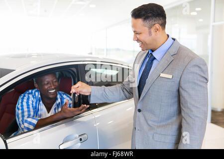 car salesman handing over new car key to customer sitting inside vehicle at showroom - Stock Image