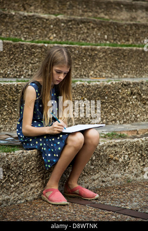 Girl writing, drawing on the stone steps - Stock Image