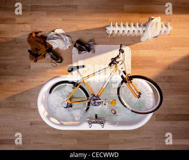 A mountain bike being cleaned in a bath. - Stock Image