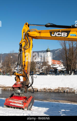 The Parish Church St. Peter and Paul in Oberammergau framed by an excavator from across the Ammer river. - Stock Image