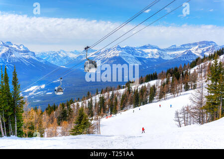 Skiing at Lake Louise in the Canadian Rockies of Alberta, Canada, with cable cars going up the mountains. - Stock Image
