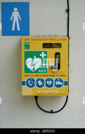 Defibrillator mounted on the wall of a male public connvenience toilet in Harrogate, North Yorkshire, England, UK. - Stock Image