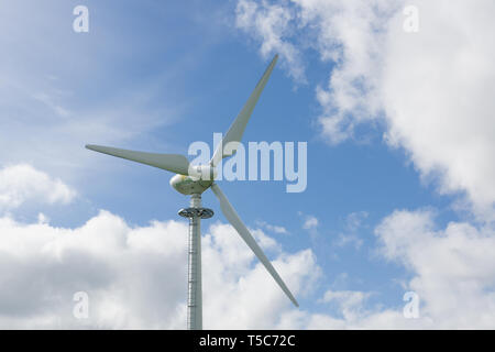 An Earthmill branded wind turbine set against a blue sky. Founded in 2009 the company specialises in service and maintenance of agricultural turbines - Stock Image