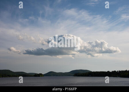 Cumulus and Cirrus clouds moving in over Lake Pleasant in the Adirondack Mountains, NY USA - Stock Image