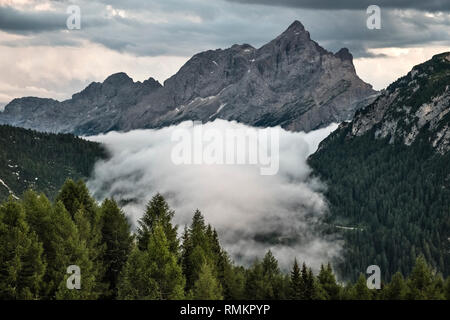 In the Italian Dolomites a temperature inversion causes a valley to fill with cloud - Stock Image