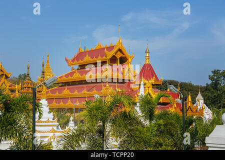 Kyauk Taw Gyi Pagoda at the foot of Mandalay Hill, Mandalay, Myanmar (Burma) with golden roof finishes on a sunny day with blue sky - Stock Image
