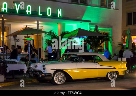Two-tone yellow and white 1955 convertible Oldsmobile Olds Super 88 hot rod and Avalon Hotel along Deco Drive, Miami - Stock Image