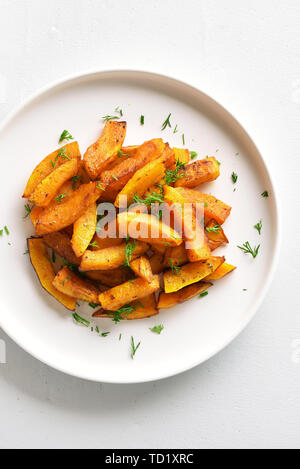 Roasted pumpkin slices on plate over white stone background. Healthy vegetarian, vegan food. Top view, flat lay - Stock Image