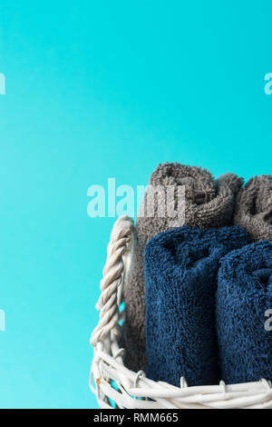 Rolled clean navy blue beige terry towels in white wicker basket turquoise wall background. Laundry spa wellness cleanliness ergonomic storage concept - Stock Image