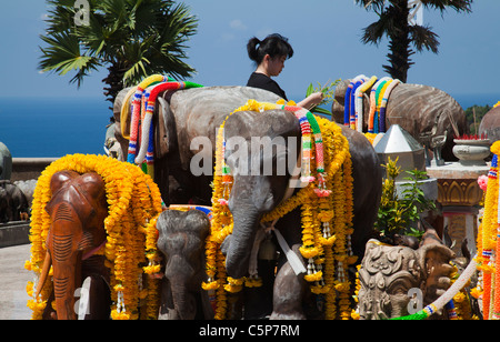 Thai Buddhist praying at open air Buddhist temple devoted to sacred elephants at Cape Promthep. - Stock Image