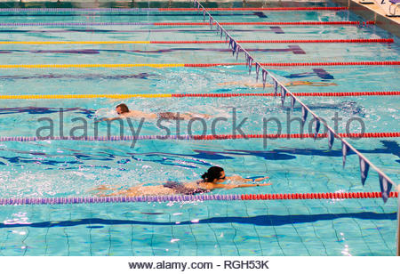 Poznan, Poland - January 26, 2019: Woman and man swimming in a pool in the Termy Maltanskie. - Stock Image
