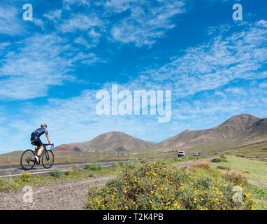 Cyclist on the long climb up to Femes village on Lanzarote, Canary Islands, Spain - Stock Image