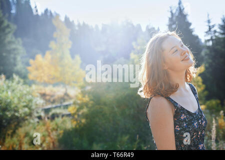 Portrait carefree young woman in sunny park - Stock Image