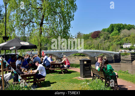 People sitting outside The Riverside Wine Bar with Chepstow bridge crossing the River Wye beyond - Stock Image