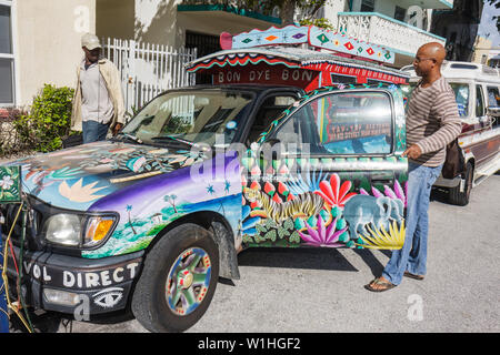 Miami Beach Florida Tap-tap cab camionette Haiti Haitian shared taxi Black man driver parked colorful landscape painted decorate - Stock Image