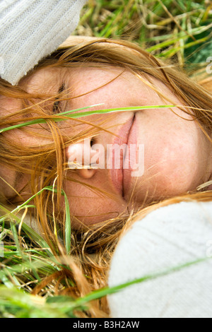 Close up portrait of attractive young redheaded woman lying in grass resting - Stock Image