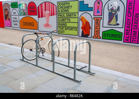 Kings Cross, London, England UK - November 2018: Fixed gear road hipster bike parked in front of billboards promoting the new venue Coal Drops Yard on - Stock Image