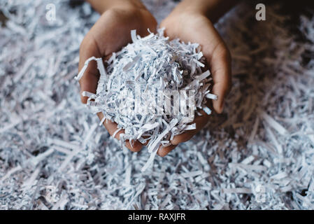 hand showing heap of shredded paper. Concept of recycle and office work of confidential - Stock Image