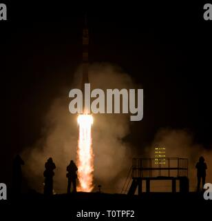 Photographers are silhouetted by the ignition flames from the Russian Soyuz MS-12 rocket as it blasts off from the Baikonur Cosmodrome March 15, 2019 in Baikonur, Kazakhstan. The Expedition 59 crew: Nick Hague and Christina Koch of NASA and Alexey Ovchinin of Roscosmos will launch March 14th for a six-and-a-half month mission on the International Space Station. - Stock Image