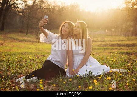 Best friends take selfie on smartphone while walking on a spring evening in park. Girls sit on a sunny glade among primroses - Stock Image