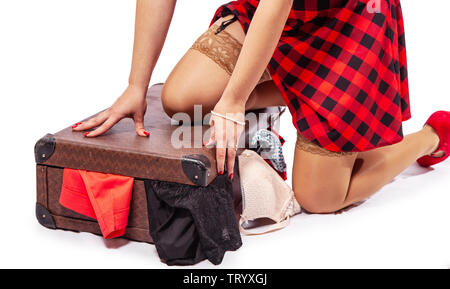 woman in red dress and nylon stockings putting clothes in a suitcase  isolated on white. legs closeup - Stock Image