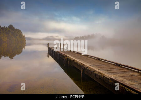 A jetty on a calm Lake Mapourika, New Zealand, with mist drifting across at dawn. - Stock Image